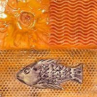 art tile of fish in shades of orange and bronze