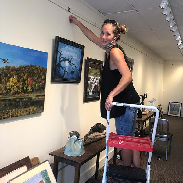 image of a volunteer hanging a painting for an upcoming show